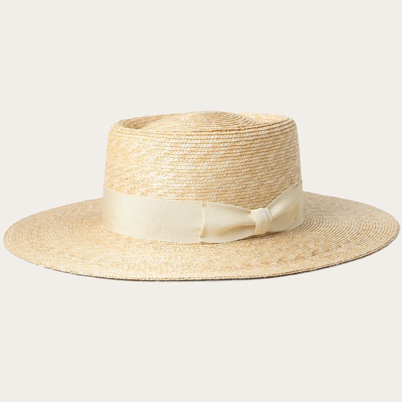 oblique view of wide brim straw garden hat with white bow ribbon