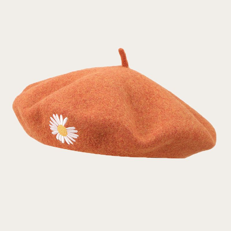 oblique view of maroon beret with embroidered flower logo