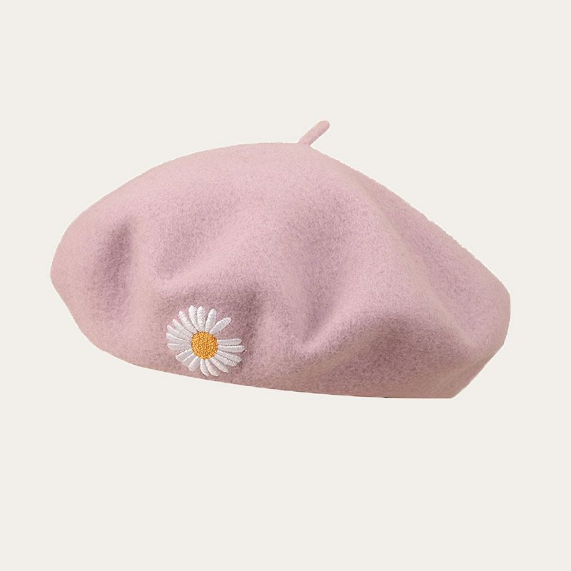 oblique view of purple beret with embroidered flower logo