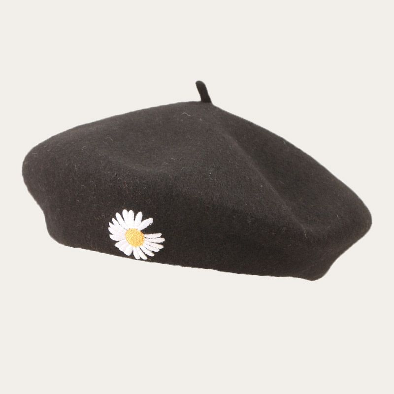 oblique view of black beret with embroidered flower logo