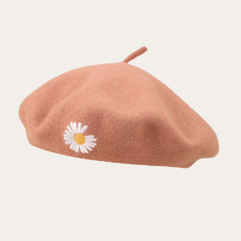 oblique view of light orange beret with embroidered flower logo