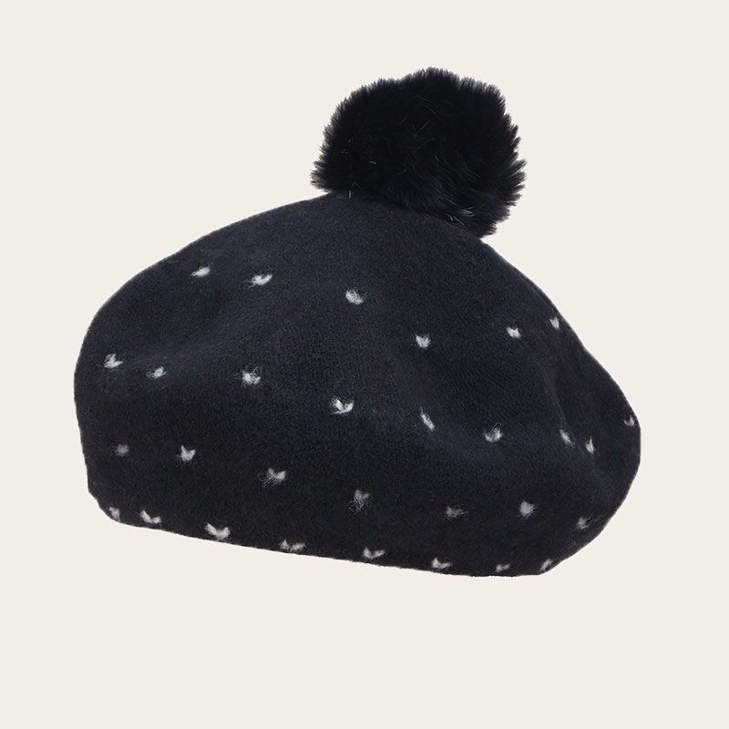 oblique view of knitted black pom pom beret with white decoration point